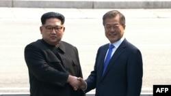 Кадр із відео корейського телебачення: північнокорейських лідер Кім Чен Ин і президент Південної Кореї Мун Чже Ін тиснуть руки біля демаркаційної лінії, що розділяє держави, 27 квітня 2018 року