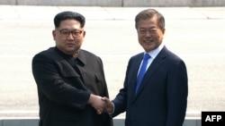 Солтүстік Корея басшысы Ким Чен Ын (сол жақта) Оңтүстік Корея президенті Мун Чжэ Инмен қол алысып тұр. 27 сәуір 2018 жыл.