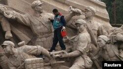 Рабочий чистит памятники на площади Тяньаньмэнь. Пекин, 1 ноября 2013 года.