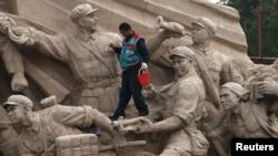 Тяньаньмэнь алаңындағы ескерткішті тазартып жүрген жұмысшы. Пекин, 1 қараша 2013 жыл.