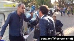 Activistul Andrei Donică (stânga) după ce a vărsat lapte peste ex-ministrul finanțelor Octavian Armașu