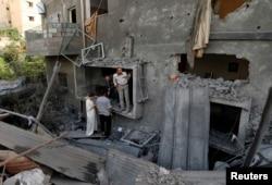 Qəzzada İsrail bombardmanında dağılmış evi sakinlər axtarırlar. 12 iyul 2014