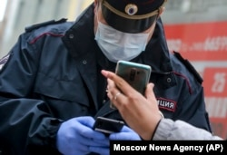 "A Russian police officer, wearing a face mask to protect against the coronavirus, checks a woman's ""digital permit"" to be on the streets of Moscow via a QR code on her smartphone."