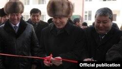 Қырғызстан президенті Алмазбек Атамбаев (ортада) және Ош қаласының әкімі Мелис Мырзакматов (оң жақ шетте) тұрғын үйдің ашылу шарасы кезінде. Ош, 17 ақпан 2012 жыл.