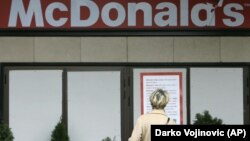 A woman reads a Latin-script sign at a McDonald's restaurant in downtown Belgrade. (file photo)