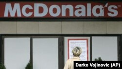 Белградтағы McDonald's-тың жабық ресторанына қарап тұрған әйел