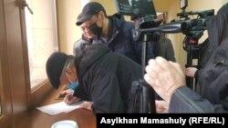 Коронавирусқа байланысты билікке жолдайтын хатқа қол қойып жатқан белсенділер. Алматы, 6 наурыз 2020 жыл.