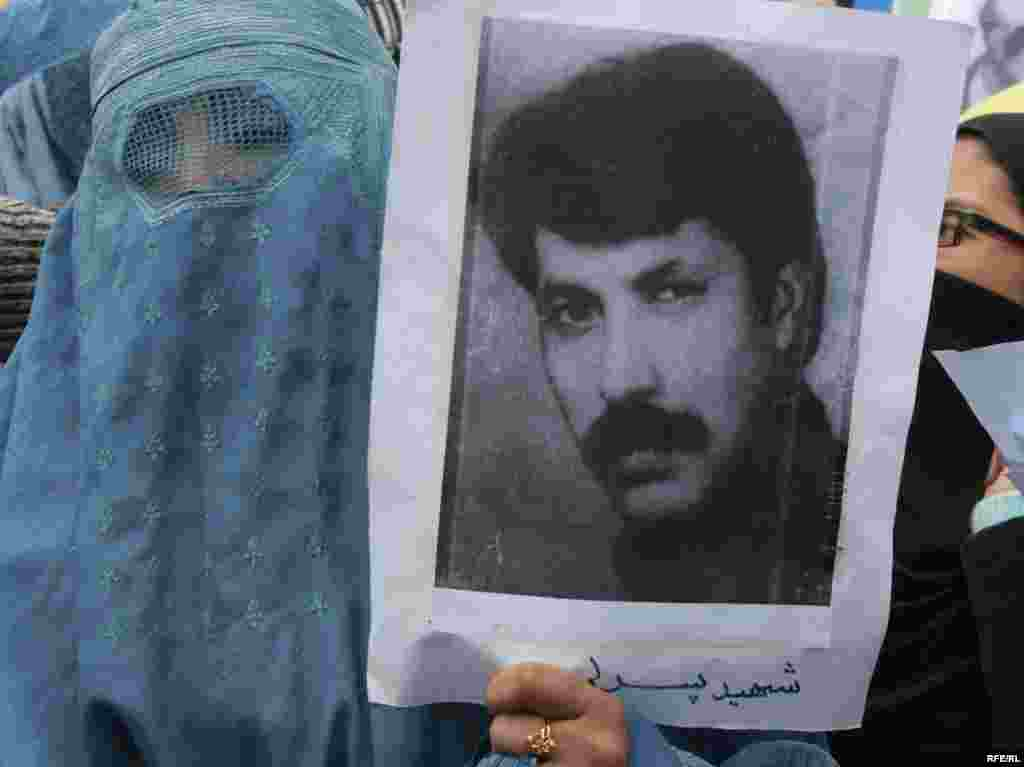 An Afghan woman holds a picture of a war victim during an antiwar protest. - Afghans gathered in Kabul on December 10 to demand that war criminals from three decades of war in Afghanistan be brought to justice. Photo by RFE/RL