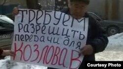 """Активист незарегистрированной оппозиционной партии """"Алга"""" Мухтар Жиенбаев проводит одиночный пикет у здания ДКНБ. Алматы, 15 февраля 2012 года."""