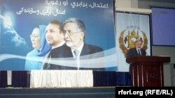 Президенттікке үміткер Залмай Расул сайлау кампаниясы плакаты алдында сөйлеп тұр.
