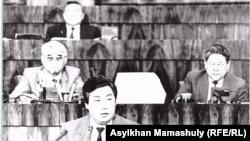 Марат Оспанов выступает в Верховном Совете 12-го созыва. В верхнем ряду за его спиной — Нурсултан Назарбаев.