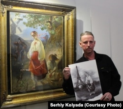 Serhiy Kolyada holds one of his works in front of a painting by 19th century poet and artist Taras Shevchenko, both featuring a figure named Kateryna.