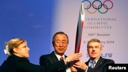 A staff member (left) adjusts the Olympic Torch while UN Secretary-General Ban Ki-moon (center) poses with International Olympic Committee (IOC) President Thomas Bach ahead of an IOC session in Sochi on February 6.