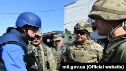 U.K, Secretary of State for Defense Gavin Willamson (left) meets with Ukrainian troops in the eastern Donbas region earlier this week.