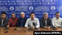 Zhanbolat Mamai (center) and other members of the Democratic Party of Kazakhstan talk to reporters in Almaty on February 19.