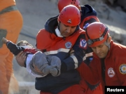 A rescue worker carries a young boy to an ambulance after he was found alive in a collapsed building in Ercis on October 24.