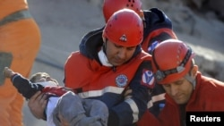 Turkey -- A rescue worker carries a boy to an ambulance after his team found him alive in a collapsed building in Ercis, 24Oct2011