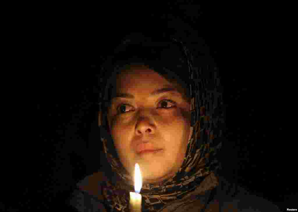 A woman holds a candle as she waits for the seven coffins during a protest procession in Kabul on November 10.