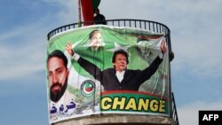 A Pakistani policeman stands guard on top of a water tank during an election campaign meeting by cricket legend and Pakistan Tehrik-e Insaaf party leader Imran Khan in the northwestern town of Mansehra on May 3.