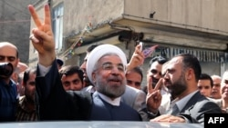 Hassan Rohani flashes a victory sign as he leaves a polling station after voting in Tehran on June 14.