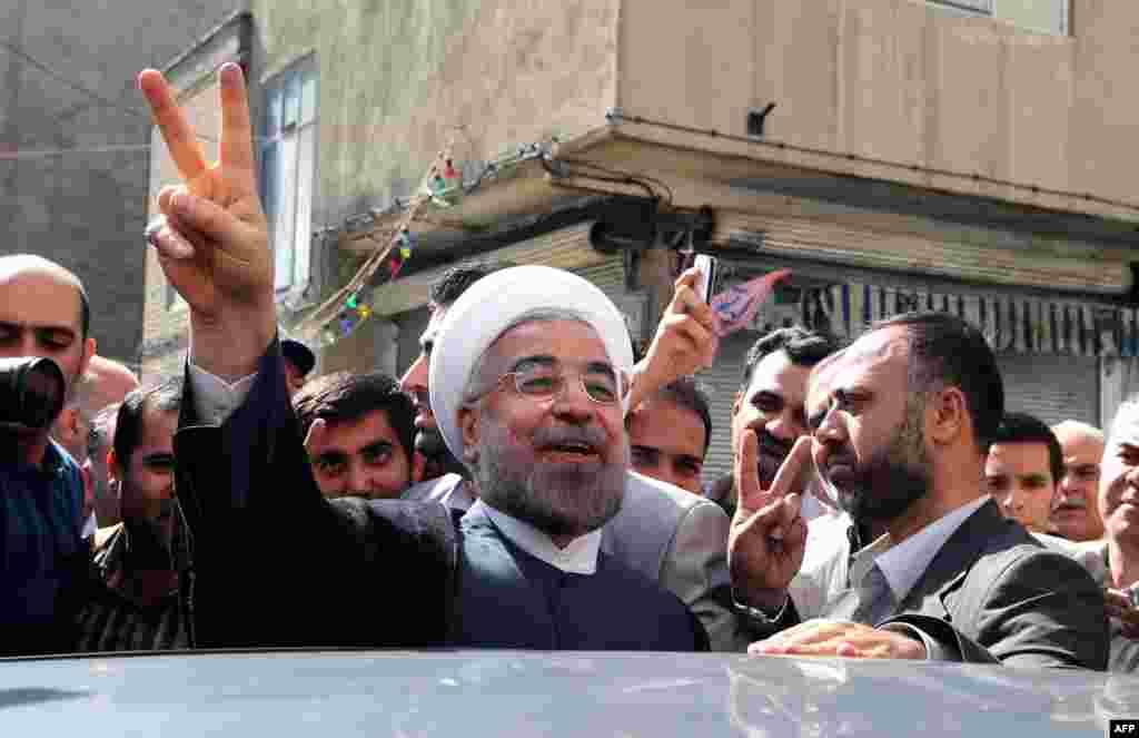 Рохани показывает знак «V», обозначающий победу, после выхода из избирательного участка в Тегеране.