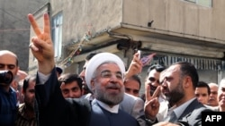 Iranian moderate presidential candidate Hassan Rohani (center) flashes the sign of victory as he leaves a polling station after voting in Tehran on June 14.