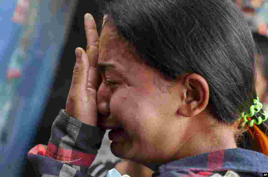 Thae Nu Naing, sister of Saw Pyae Naing weeps by his body at their home in Mandalay, Myanmar, Sunday, March 14, 2021.Saw Pyae Naing, a 21-year old anti-coup protester was shot and killed by Myanmar security forces during a demonstration on Saturday, according to his family.