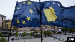 Kosovar Albanians walk under the EU and Kosovo flags in the main square of Pristina on May 4.