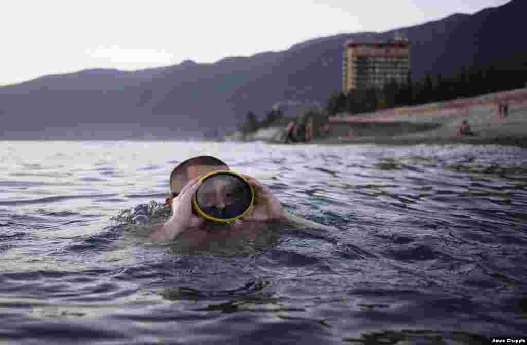 Vladimir Salangin swims near Gagra beach. The 21-year-old works as a security guard in southern Russia and saw the sea for the first time the day before this picture was taken. The cheap resort town of Gagra is hugely popular with working-class Russians.