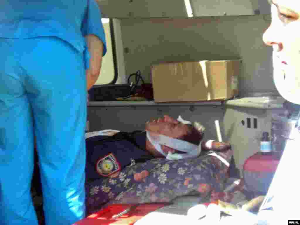 Этого полицейского жители доставили до машины скорой медицинской помощи.