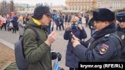 Константин Котов общается с российским полицеским в ходе одиночного пикета в центре Москвы, 17 марта 2019 года