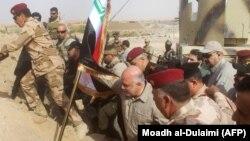 Прем'єр-міністр Іраку Хайдар аль-Абаді (с) йде встановлювати прапор країни в місті Аль-Каїм, що за кілька кілометрів від Румани, визволене попередніми днями, фото 5 листопада 2017 року
