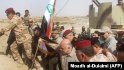 Iraqi Prime Minister Haidar al-Abadi erects a national flag in Al-Qaim after the town was retaken by government forces from the extremist group Islamic State earlier this month.