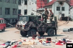 A picture dated July 16, 1995, shows Bosnian Serb fighters driving through the empty streets of Srebrenica after Ratko Mladic's troops had overrun this UN safe area the previous week.