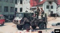 На снимке, датированном 16 июля 1995 года, бойцы боснийских сербов, проезжающие по пустым улицам Сребреницы после того, как войска Ратко Младича за неделю до этого вторглись в «безопасную зону» ООН.