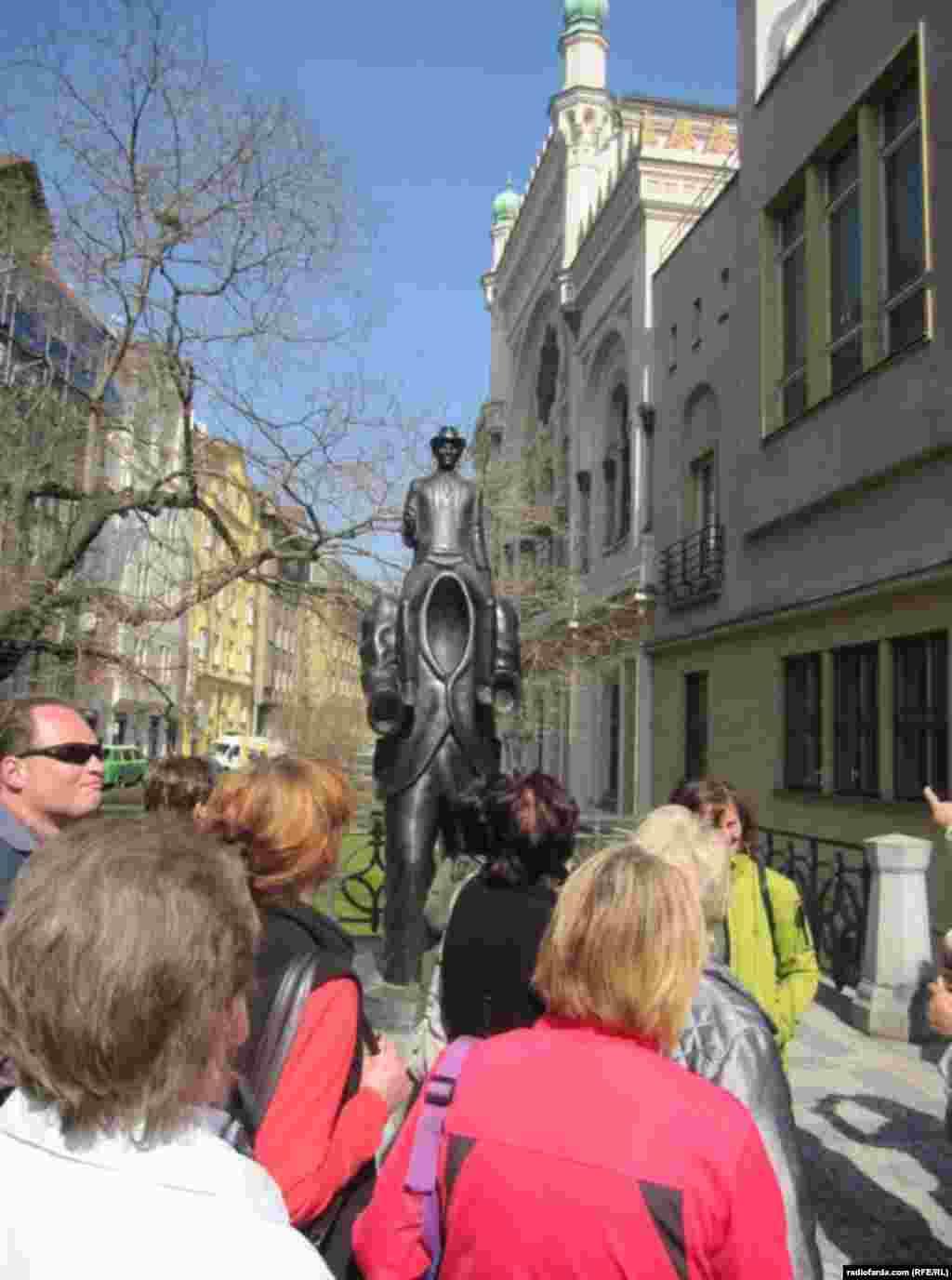 نمای دیگری از تندیس یادبود کافکا در کنار کنیسه اسپانیاییها و گردشگران مشتاق