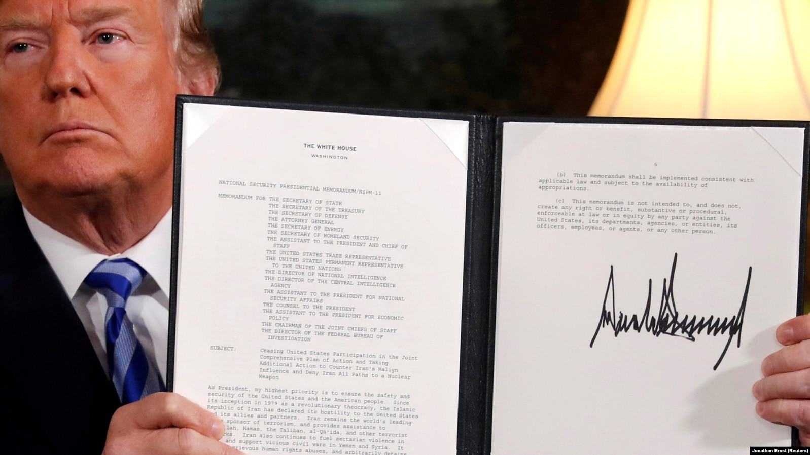 U.S. -- U.S. President Donald Trump holds up a proclamation declaring his intention to withdraw from the JCPOA Iran nuclear agreement after signing it in the Diplomatic Room at the White House in Washington, U.S. May 8, 2018.