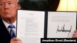 U.S. President Donald Trump holds up a proclamation declaring his intention to withdraw from the Iran nuclear agreement after signing it in the Diplomatic Room at the White House in Washington on May 8.