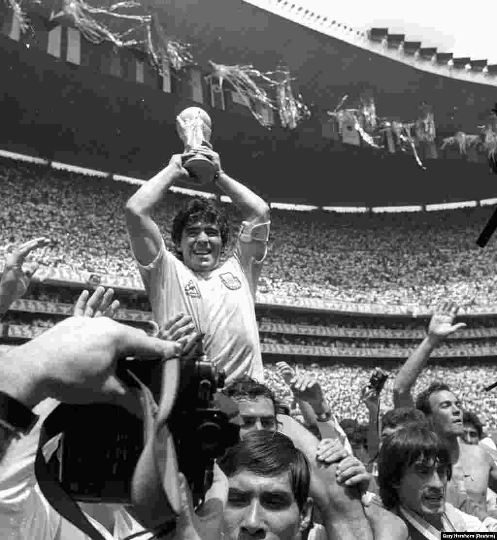 Diego Maradona magasra emeli a világbajnokoknak járó trófeát, miközben a tömeg az 1986-ban aratott győzelmüket ünnepli.