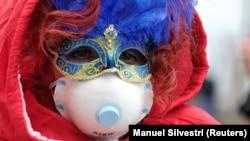 Участник Венецианского карнавала в костюме и защитной маске, Венеция, 23 февраля 2020 года.