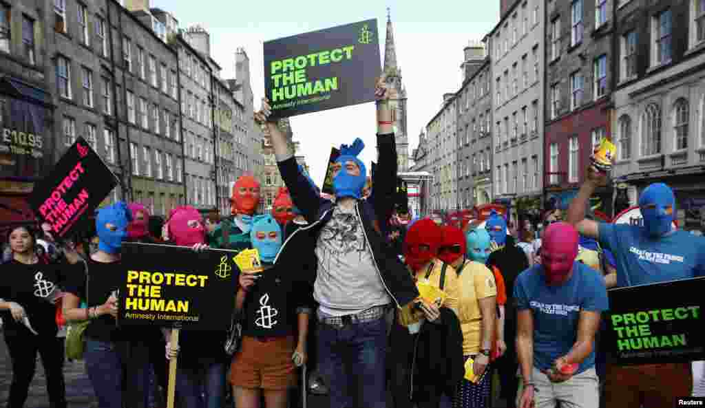 Protesters wearing masks take part in an Amnesty International flash-mob demonstration in support of Pussy Riot in Edinburgh on August 14.