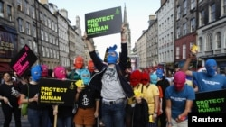 Protesters wearing Pussy Riot's signature balaclavas take part in an Amnesty International flash-mob demonstration in support of the punk group in Edinburgh, Scotland on August 14.