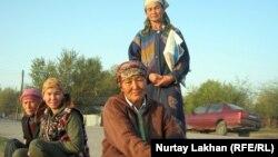 Женщины-репатриантки, сидящие вдоль дороги, нанимаются на поденную работу. Село Жалгамыс Алматинской области, 17 октября 2011 года. Иллюстративное фото.