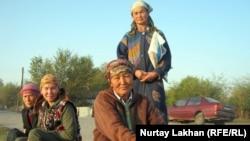 Женщины-оралманки на обочине дороги ждут случайного работодателя. Город Талгар, Алматинская область.