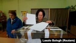 Избирательница опускает бюллетень в урну в день парламентских выборов в Болгарии. София, 26 марта 2017 года.