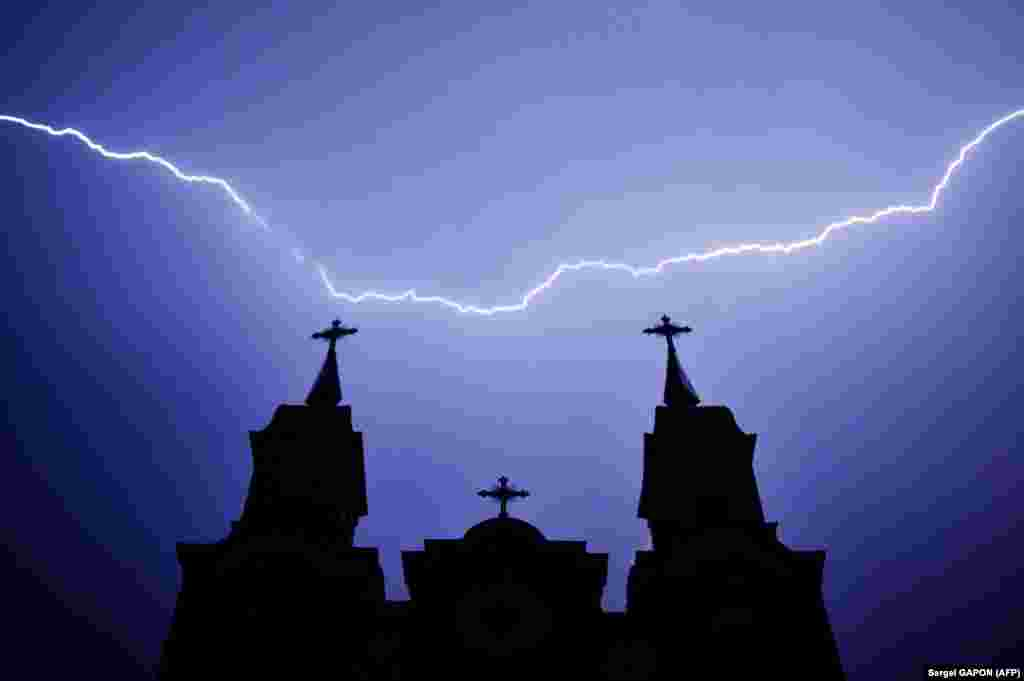 Lightning strikes above a Catholic church during a thunderstorm in the Belarusian village of Kreva, some 100 kilometers northwest of Minsk. (AFP/Sergei Gapon)