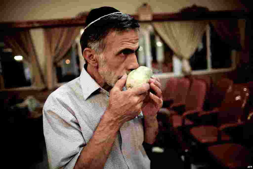An Iranian Jew inspects a special lemon (etrog) used during the celebration of Sukkot, the feast of the Tabernacles, to be blessed at a synagogue in downtown Tehran.