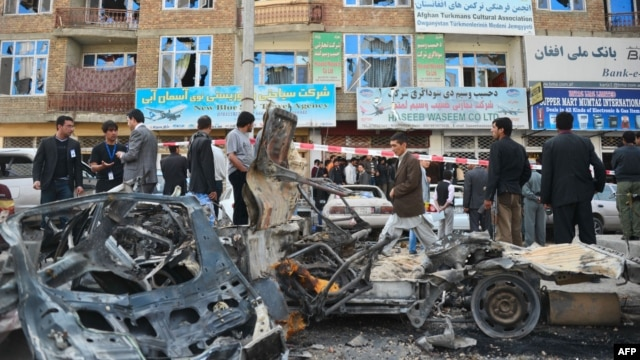 Afghan security personnel on April 16 cordon off the wreckage of cars in front of a building damaged by one of the Kabul attacks.