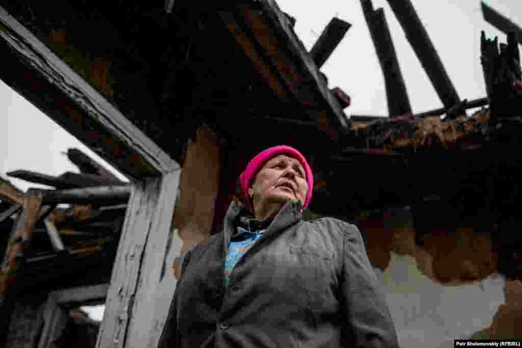 Demianenko stands inside the ruins of her house.