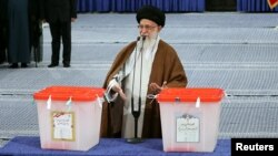 Iranian Supreme Leader Ayatollah Ali Khamenei gestures as he casts his vote during the presidential election in Tehran on May 19.